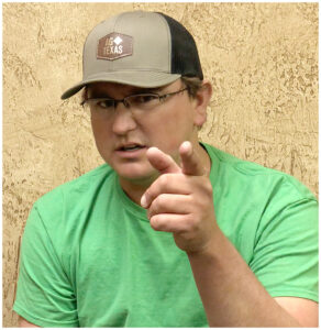 Kalan wearing an AgTexas cap - pointing at the camera in a friendly gesture