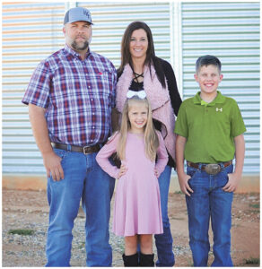 The Kimbrell family standing outside in front of a grain silo