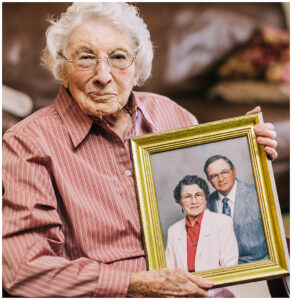 Margaret Russell holding an older framed picture of her and her late husband, L.J. Russell
