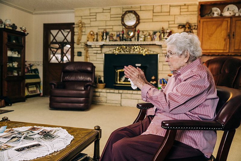 Margaret sitting in her living room preparing to tell us some of her story. Fireplace in the background and cozy room.