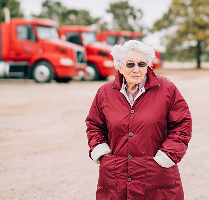 Margaret Russell bundled up in her warm coat as she poses outside in front of her delivery trucks- in Texhoma, OK